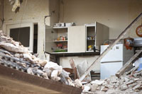 a kitchen surrounded by earthquake rubble